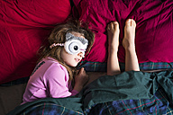 Girl with sleep mask and barefoot legs of another person side by side on bed - XCF00145