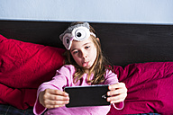 Girl lying on bed taking selfie with cell phone - XCF00151
