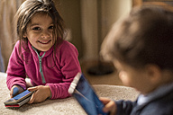 Portrait of smiling little girl with smartphone - JASF01563