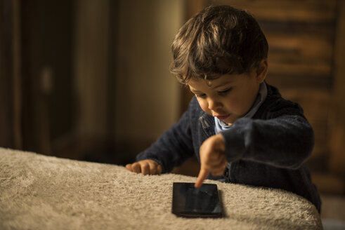 Toddler playing with smartphone at home - JASF01566