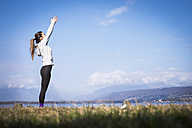 Woman practicing yoga at a lake raising her arms - SIPF01462