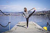 Woman practicing yoga on a pier at a lake - SIPF01468