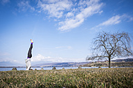 Woman practicing yoga doing a headstand at a lake - SIPF01471
