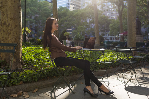 USA, New York, Manhattan, young businesswoman with laptop sitting at table in a park - BOYF00691