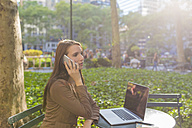 USA, New York, Manhattan, young businesswoman on the phone sitting at table in a park - BOYF00697
