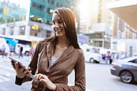 USA, New York, Manhattan, smiling young businesswoman with tablet on the street - BOYF00718