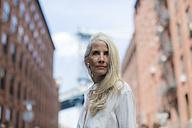 USA, Brooklyn, Dumbo, portrait of mature woman wearing white shirt blouse - GIOF02274