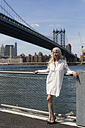 USA, Brooklyn, mature woman standing in front of East River and Manhattan Bridge - GIOF02277
