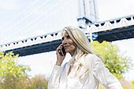 USA, Brooklyn, mature woman on the phone in front of Manhattan Bridge - GIOF02289