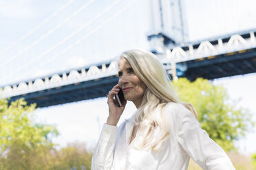 USA, Brooklyn, mature woman on the phone in front of Manhattan Bridge - GIOF02289