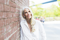 Portrait of smiling mature woman wearing white shirt blouse leaning against brick wall - GIOF02292