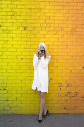 Mature woman leaning against coloured wall taking picture with camera - GIOF02301