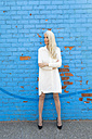 Mature woman wearing white dress standing in front of light blue wall - GIOF02304