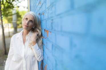 Portrait of daydreaming mature woman leaning against light blue wall - GIOF02307