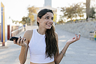 Portrait of grinning young woman with cell phone - GIOF02323