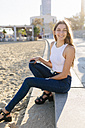 Spain, Barcelona, portrait of smiling young woman sitting on beach promenade at sunset - GIOF02329