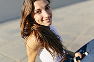 Portrait of smiling young woman at sunset - GIOF02332