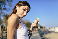 Young woman relaxing on beach promenade at sunset listening music with earphones - GIOF02338