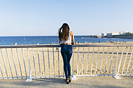 Back view of young woman standing on beach promenade looking to the sea - GIOF02341