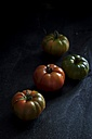 Four tomatoes on black wood - YFF00658