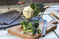 Broccoli florets and kitchen knife on wooden board - YFF00661
