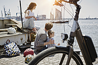Germany, Hamburg, family having a break from a bicycle tour at River Elbe - RORF00683