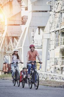Germany, Hamburg, family riding e-bikes at the harbor - RORF00698
