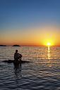 Spain, Menorca, Playa de Cavalleria, man on rock in the sea at sunset - SMAF00726
