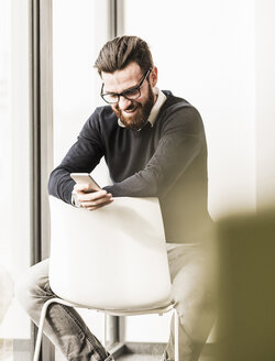 Young businessman sitting on chair using smart phone - UUF10147