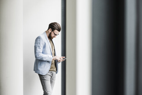Young businessman standing in office, using smart phone - UUF10150