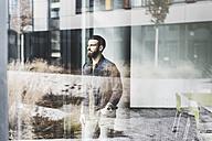 Young businessman standing at window pane, wearing smart watch - UUF10156