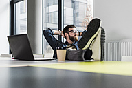 Young casual businessman sitting in office with feet up and a cup of coffee - UUF10162