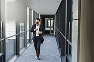 Businessman with earphones talking on smart phone in office building - UUF10171
