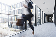 Businessman running in corridor of an office building - UUF10177