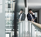 Businessman standing in office building, using smart phone and digital tablet - UUF10183