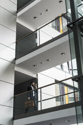 Businessman walking in office building, while using smart phone - UUF10186