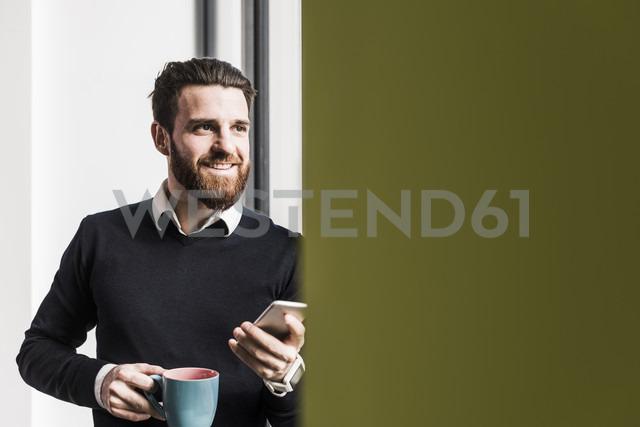 Businessman holding smart phone, talking - UUF10192 - Uwe Umstätter/Westend61