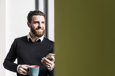 Businessman holding smart phone, talking - UUF10192