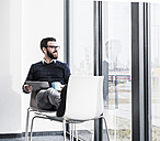 Young businessman sitting on chair using digital tablet - UUF10195