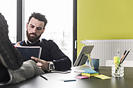 Businessman sitting in office reading files - UUF10204