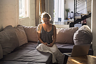 Blond woman sitting on the couch at looking at cell phone - KNTF00812