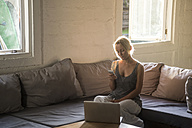 Blond woman sitting on the couch looking at cell phone - KNTF00815