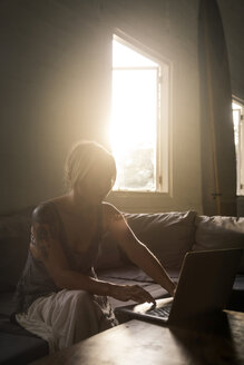 Blond woman sitting on the couch at backlight using laptop - KNTF00818