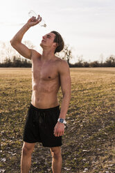 Barechested athlete in rural landscape pouring water over his face - UUF10218