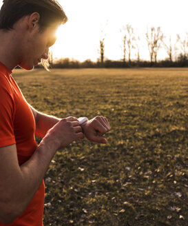 Athlete in rural landscape looking on smartwatch - UUF10224