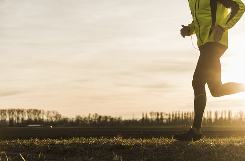 Man running in rural landscape at sunset - UUF10227