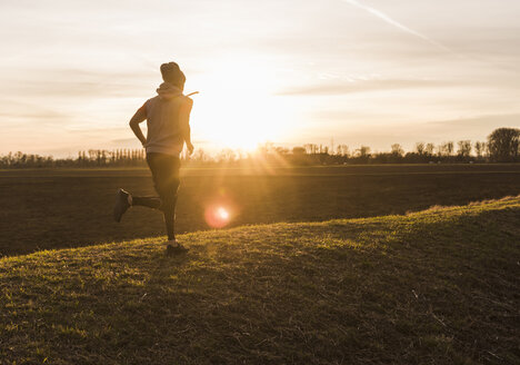 Man running in rural landscape at sunset - UUF10230