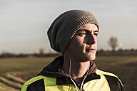 Portrait of athlete wearing wooly hat and earphones - UUF10233