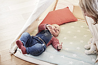Happy baby girl lying on blanket looking at grandmother - FMKF03579