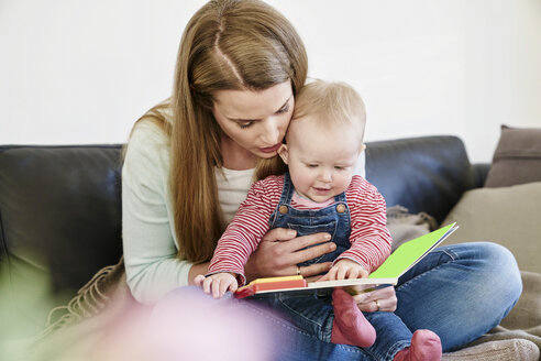 Mother and baby girl at home looking at book - FMKF03582